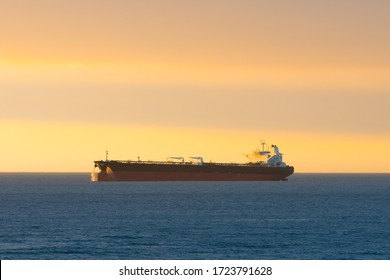 Cargo ship at sunset in the coasts of Chile outside the port of Valparaiso.