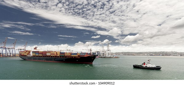 Cargo ship with tug boat assistance leaving the port of Durban South Africa
