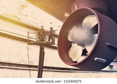 Cargo ship under repair by jet high pressure water jet on propeller of ship to cleaning before blasting and planting in shipyard on Monochrome