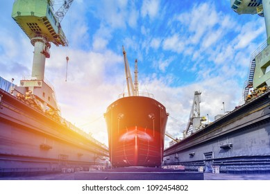 Cargo ship under repair sandblasted and painting at floating dry dock in shipyard