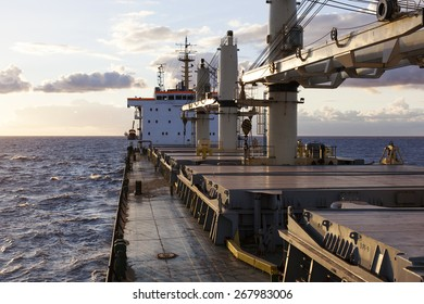 Cargo ship underway on the Pacific ocean against sunset