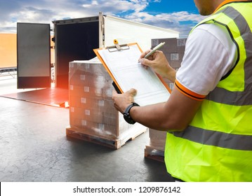 Cargo shipment loading for truck. Road freight truck logistics and transportation. Warehouse worker courier holding clipboard inspecting document cargo shipment pallets for load into a truck.