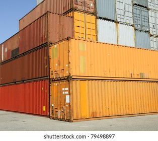 Cargo shipping containers stacked at harbor freight terminal under clear blue sky