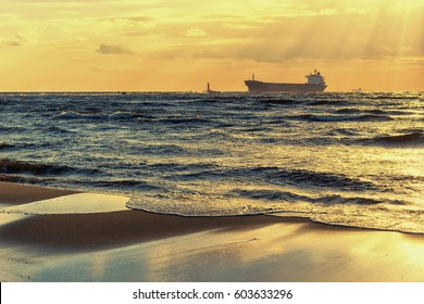 Cargo ships are in the Baltic sea at sunset past the lighthouse against the sky with sun rays