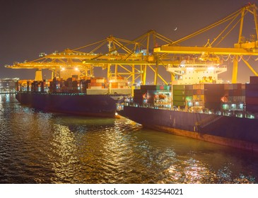 Cargo ships, cranes and containers at industrial sea port at night. Barcelona, Spain