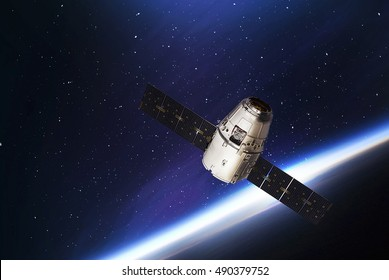 Cargo spaceship in the space and earth on the background. Elements of earth on this image furnished by NASA. Astronomy and outer space conception. Distant galaxies and space dream. Cosmos. Spacecraft