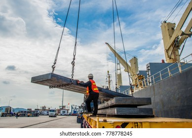 cargo steel slab discharging from the ship vessel laying onto the lorry trailer tier to tier, the shipment export and import under logistics system services to global worldwide transportation