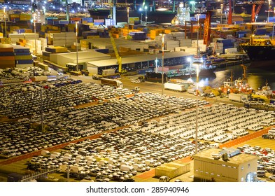 Cargo terminal in industrial port with containers and cars.
