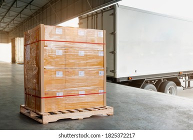 Cargo trailer truck parked loading at dock warehouse. Freight truck. Shipment. Delivery service. Package boxes on  pallet waiting to load into container truck. Logistics and Transportation.