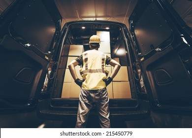 Cargo Van Delivery. Rear Cargo Doors Reloading. Construction Guy Talking Care of Fresh Supplies Delivery. Large Cargo Van with Many Cardboard  Boxes Waiting For Reload.