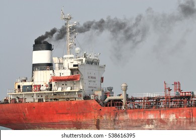 Cargo vessel belching smoke while traveling up Malacca Strait in Malaysia