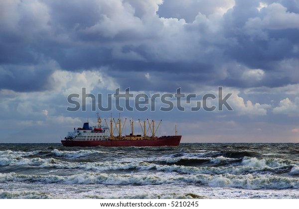 cargo vessel in the stormy sea under the cloudy skies