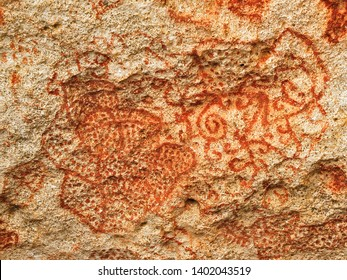 Carib or Arawak cave paintings in red dye on a rock wall, authentic pre-Columbian art in Caribbean Islands.
