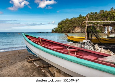 Caribbean bay with fishing boats of yellow and teal and coral colors