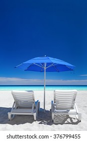 Caribbean beach with blue sun umbrellas and white beds. Tropical vacation