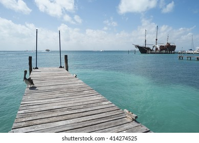Caribbean beach landscape, clear turquoise water with pelican bird on wood pier bridge and old nautical ship in the distance.