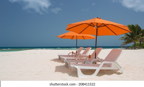 Caribbean Beach with Lounge Chairs and Umbrellas