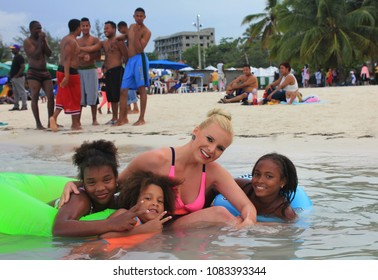CARIBBEAN – DOMINICAN REPUBLIC – FEBRUARY 2017 - Lenka Kopalova on the beach in Boca Chica (Santo Domingo) with Dominican and Haitian children on Public Holiday - Independence Day.