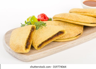 Caribbean Jerk Beef Patty - Jamaican spicy minced jerk beef with onions and peppers in short crust pastry and scotch bonnet chillies on a white background.