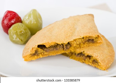 Caribbean Lamb Pattie - Jamaican spicy minced lamb with onions and peppers in short crust pastry and scotch bonnet chillies on a white background.