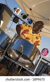 A Caribbean musician jamming on his steel drums.