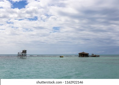 In the Caribbean Ocean 1 Mile NW Of Treasure Beach, Jamaica - January 30, 2014: Floyd's Pelican Bar is a tiny bar made of driftwood stilted on a huge sandbar about ¾ miles out in the sea.
