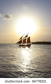 a caribbean pirate vessel with a sunset backdrop on the horizon