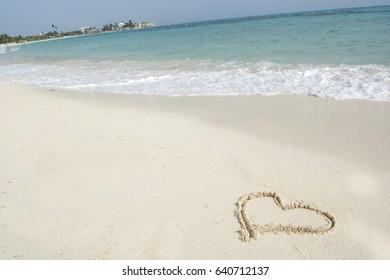 Caribbean tropical beach with a big heart drawn on white sand.
