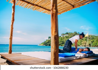 Caribbean turquoise beach with two woman doing massage therapy