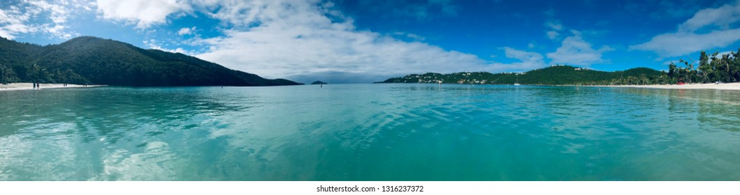 Caribbean vacation, panoramic beach lagoon - direct water closeup, blue sky and mountains in distance