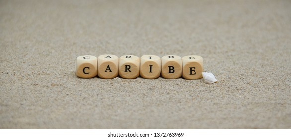 caribe word built with wooden cubes and black letters on the floor and bottom of sand beach