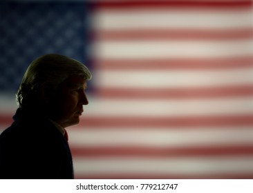 Caricature silhouette of United States President Donald Trump looking down in front of a United States flag. Soft focus effect.