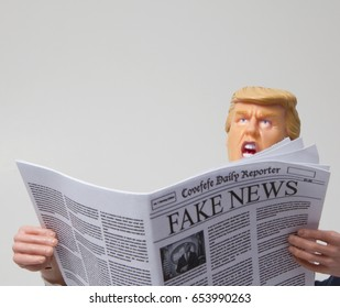 Caricature of United States President Donald Trump reading a Fake News newspaper - shouting - anger concept - action figure toy