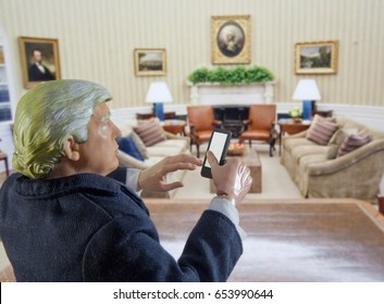 Caricature of United States President Donald Trump in the White House Oval Office using a mobile device - Twitter / tweeting concept - action figure toy