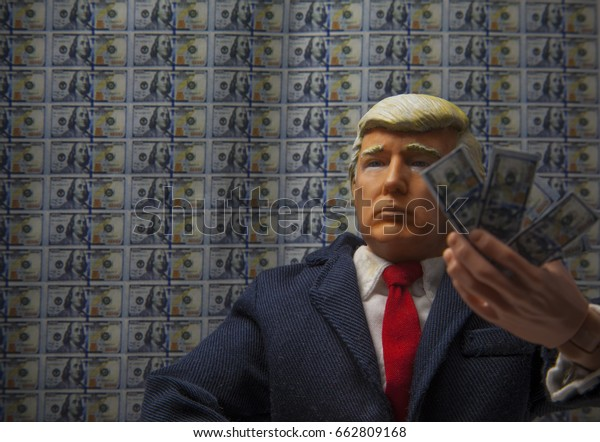 A caricature of United States President Donald Trump holding 100 dollar bills standing in front of a sheet of $100 bills using a plastic toy action figure doll