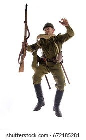 Caricatured changes Male actor in uniform and helmet ordinary soldier of Russian army during World War I posing, jumping and running on white background in studio