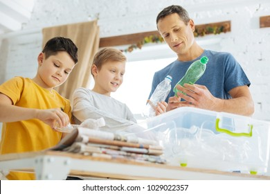 Caring about nature. Charming young man and his pre-teen sons preparing plastic bottles for recycling, crushing the bottles and putting them into special containers