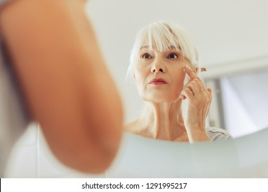 Caring about skin. Reflection of a nice aged woman while putting on cream