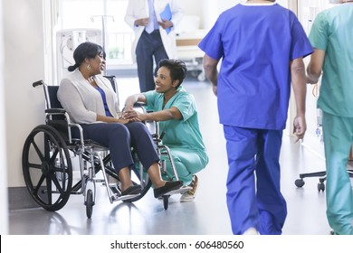 Caring African American female nurse in hospital uniform scrubs with wheelchair patient in medical centre