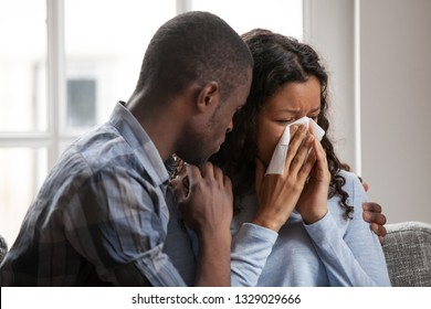 Caring African American husband cheering upset crying wife wiping nose, loving black boyfriend caress support mixed race girlfriend suffering feeling down, supportive man hug spouse showing empathy
