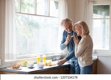 Caring aged husband feed loving senior wife hugging him from behind, elderly romantic couple cook breakfast at home together, sensual man treat beloved woman embracing making food in kitchen