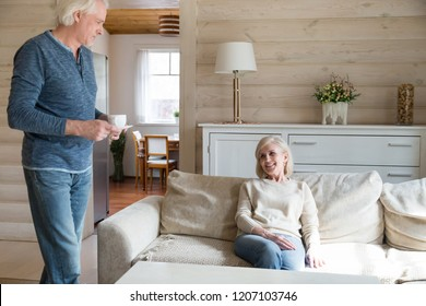 Caring aged husband making tea for beloved wife spending weekend in countryside, loving senior man bring hot drink to elderly smiling woman relaxing at home together. Successful marriage concept