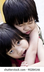 Caring Asian Sister carrying injured little brother