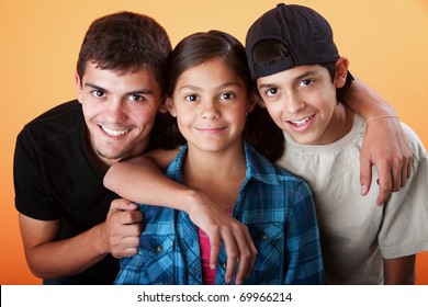 Caring brothers with their sister smiling on orange background
