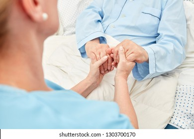 Caring caregiver holds the hands of a sick elderly person as terminal care