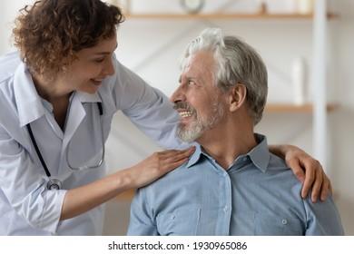 Caring Caucasian female nurse support caress optimistic overjoyed senior Caucasian man patient. Smiling woman doctor comfort mature male during home visit. Elderly healthcare, geriatrics concept.