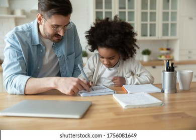 Caring Caucasian stepfather help with homework adorable mixed-race daughter. Home tutor teaches school subject to little learner, sitting together in domestic kitchen. Education, homeschooling concept