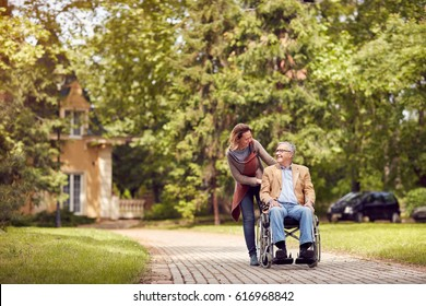 caring daughter and senior man in wheelchair on walking green nature
