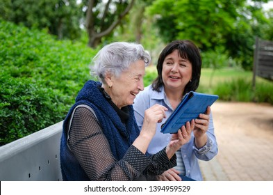Caring daughter teaching her elderly mother how to use a tablet in social networks