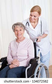 Caring Doctor Helping Handicapped Senior Patient Indoors